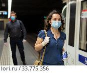 Купить «Woman in mask with earphones on subway station», фото № 33775356, снято 26 мая 2020 г. (c) Яков Филимонов / Фотобанк Лори