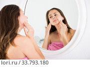 Купить «Young woman touching face and using mirror in bedroom», фото № 33793180, снято 1 июня 2020 г. (c) Яков Филимонов / Фотобанк Лори