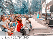 """Russia, Samara, July 2017: young people listen to a lecture on the embankment at the festival """"Volgafest"""" on a summer day. Text in Russian: today the factories are turning into lofts. Редакционное фото, фотограф Акиньшин Владимир / Фотобанк Лори"""