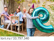 Mädchen feiert Geburtstag im Garten im Sommer mit Luftballon mit der Zahl Neun. Стоковое фото, фотограф Zoonar.com/Robert Kneschke / age Fotostock / Фотобанк Лори