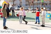 Children skipping on elastic jump rope. Стоковое фото, фотограф Яков Филимонов / Фотобанк Лори