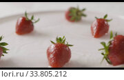 Купить «Ripe red strawberry fruit falls into the center of a plate of water with splashes and drops of water. A few berries lie on the white plate. Slow motion. Out of focus. Full HD video, 240fps,1080p.», видеоролик № 33805212, снято 29 июня 2018 г. (c) Ярослав Данильченко / Фотобанк Лори