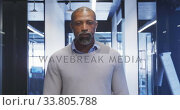 Купить «Businessman walking and looking at camera in modern office», видеоролик № 33805788, снято 12 октября 2019 г. (c) Wavebreak Media / Фотобанк Лори