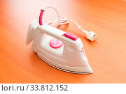Купить «Modern electric iron on the wooden background», фото № 33812152, снято 16 июля 2020 г. (c) age Fotostock / Фотобанк Лори