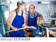Experienced worker helping girl in work on circular saw. Стоковое фото, фотограф Яков Филимонов / Фотобанк Лори