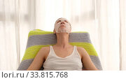 Adult female with moisturizing sheet mask on face resting in comfortable armchair with closed eyes during spa procedure at home. Стоковое видео, видеограф Ekaterina Demidova / Фотобанк Лори