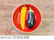 Pod of yellow pepper and almost black eggplant on a red plate on a wooden tabletop. Стоковое фото, фотограф Евгений Харитонов / Фотобанк Лори