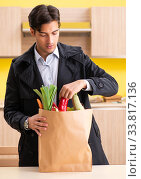 Купить «Young handsome man with vegetables in kitchen», фото № 33817136, снято 3 августа 2018 г. (c) Elnur / Фотобанк Лори