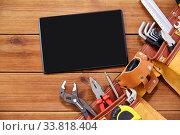Купить «tablet computer and tool belt on wooden boards», фото № 33818404, снято 26 ноября 2019 г. (c) Syda Productions / Фотобанк Лори