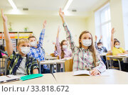 group of students in masks raising hands at school. Стоковое фото, фотограф Syda Productions / Фотобанк Лори