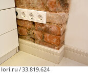 Купить «Четырехместная  розетка установлена на старой кирпичной стене в помещении», фото № 33819624, снято 19 мая 2020 г. (c) Ирина Борсученко / Фотобанк Лори