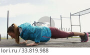 Купить «Sporty Caucasian woman exercising in an outdoor gym during daytime», видеоролик № 33819988, снято 8 августа 2019 г. (c) Wavebreak Media / Фотобанк Лори