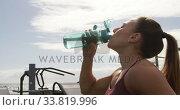 Купить «Sporty Caucasian woman drinking water in an outdoor gym during daytime», видеоролик № 33819996, снято 8 августа 2019 г. (c) Wavebreak Media / Фотобанк Лори