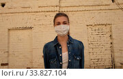 Купить «Young female wearing disposable face mask standing in front of brick building during coronavirus epidemic and looking at camera», видеоролик № 33827104, снято 14 мая 2020 г. (c) Ekaterina Demidova / Фотобанк Лори