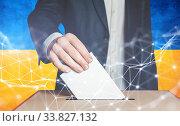 Мужчина избиратель опускает бюллетень в урну для голосования на фоне украинского флага. Стоковое фото, фотограф Сергей Тиняков / Фотобанк Лори
