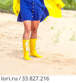 young beautiful woman walks along the beach in yellow boots and a yellow cape on a cloudy summer day. Стоковое фото, фотограф Акиньшин Владимир / Фотобанк Лори