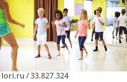 Купить «Children dancing synchronous group choreography with female coach in dance hall», видеоролик № 33827324, снято 23 мая 2020 г. (c) Яков Филимонов / Фотобанк Лори