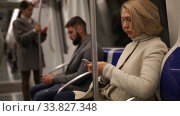 Купить «Portrait of mature woman absorbed in her smartphone while traveling in subway car», видеоролик № 33827348, снято 11 ноября 2019 г. (c) Яков Филимонов / Фотобанк Лори