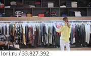 Young focused woman shopping casual clothes in modern men store. Стоковое видео, видеограф Яков Филимонов / Фотобанк Лори