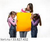 Купить «Мама и две дочки держат в руках оранжевую вывеску и смотрят на нее», фото № 33827432, снято 15 мая 2020 г. (c) Иванов Алексей / Фотобанк Лори