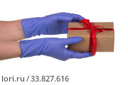 Female hand in blue latex glove holds a cardboard box of brown kraft paper on a white background, safe and contactless delivery of on-line orders during epidemics. Стоковое фото, фотограф Сергей Молодиков / Фотобанк Лори