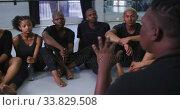 Купить «Mixed race fit male modern dancer sitting on the floor and talking to a group of dancers », видеоролик № 33829508, снято 4 декабря 2019 г. (c) Wavebreak Media / Фотобанк Лори