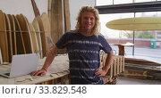 Caucasian male surfboard maker in his studio with surfboards in background. Стоковое видео, агентство Wavebreak Media / Фотобанк Лори