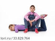 Купить «Two sad girls rest sitting and lying on a white background», фото № 33829764, снято 15 мая 2020 г. (c) Иванов Алексей / Фотобанк Лори