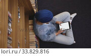 Купить «Asian female student wearing a blue hijab sitting on the floor and using tablet», видеоролик № 33829816, снято 7 июня 2019 г. (c) Wavebreak Media / Фотобанк Лори