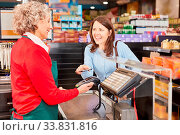 Купить «Junge Frau macht Mobile Payment mit NFC Smartphone an der Supermarkt Kasse», фото № 33831816, снято 5 июня 2020 г. (c) age Fotostock / Фотобанк Лори