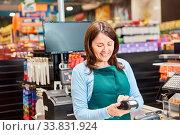Купить «Lächelnde Frau als Kassiererin mit einem Barcode-Scanner an der Supermarkt Kasse», фото № 33831924, снято 5 июня 2020 г. (c) age Fotostock / Фотобанк Лори