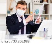 Купить «Manager in disposable mask discussing in office», фото № 33836988, снято 26 мая 2020 г. (c) Яков Филимонов / Фотобанк Лори