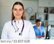 Female doctor in lab coat holding clipboard with medical records. Стоковое фото, фотограф Яков Филимонов / Фотобанк Лори