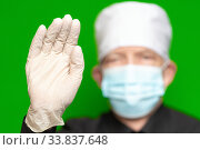Купить «Doctor male in surgical face mask on defocus foreground put forward palm of his hand in protective latex glove foreground, waves by his hand, hello or stop sign», фото № 33837648, снято 24 мая 2020 г. (c) А. А. Пирагис / Фотобанк Лори