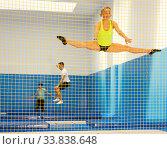 Купить «Female gymnast jumping on trampoline», фото № 33838648, снято 15 июля 2020 г. (c) Яков Филимонов / Фотобанк Лори