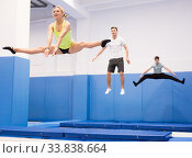 Купить «Female gymnast practicing middle split on trampoline», фото № 33838664, снято 1 февраля 2020 г. (c) Яков Филимонов / Фотобанк Лори