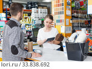 Купить «Girl seller standing at the counter in shop and helping male», фото № 33838692, снято 17 мая 2018 г. (c) Яков Филимонов / Фотобанк Лори