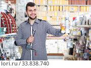 Купить «satisfied male customer examining various glue tubes in store», фото № 33838740, снято 5 апреля 2017 г. (c) Яков Филимонов / Фотобанк Лори