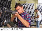 Купить «Portrait of adult male which is choosing air-powered gun», фото № 33838748, снято 4 июля 2017 г. (c) Яков Филимонов / Фотобанк Лори