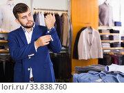 Купить «Glad male customer choosing jacket», фото № 33838760, снято 28 сентября 2017 г. (c) Яков Филимонов / Фотобанк Лори