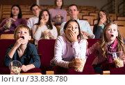 Emotional audience attending movie night with popcorn. Стоковое фото, фотограф Яков Филимонов / Фотобанк Лори