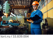 Male worker with notebook, lathe on background. Стоковое фото, фотограф Tryapitsyn Sergiy / Фотобанк Лори