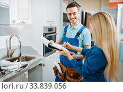 Male plumber and female customer in the kitchen. Стоковое фото, фотограф Tryapitsyn Sergiy / Фотобанк Лори