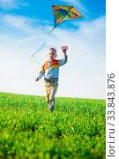 Купить «Young boy flies his kite in an open field. Little kid playing with kite on green meadow. Childhood concept.», фото № 33843876, снято 14 июля 2020 г. (c) easy Fotostock / Фотобанк Лори