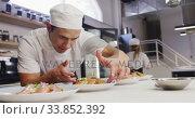 Купить «Mixed race male chef wearing chefs whites in a restaurant kitchen, putting food on a plate», видеоролик № 33852392, снято 5 декабря 2019 г. (c) Wavebreak Media / Фотобанк Лори