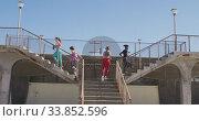 Купить «Multi-ethnic group of women running on a bridge stairs on the beach and blue sky background», видеоролик № 33852596, снято 15 октября 2019 г. (c) Wavebreak Media / Фотобанк Лори