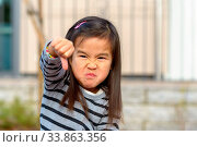 Купить «Angry frustrated little girl throwing a temper tantrum punching her fist at the camera with a furious vengeful expression outdoors», фото № 33863356, снято 28 мая 2020 г. (c) easy Fotostock / Фотобанк Лори