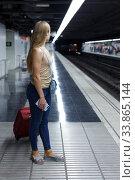 Купить «Woman on underground platform waiting train», фото № 33865144, снято 19 сентября 2018 г. (c) Яков Филимонов / Фотобанк Лори