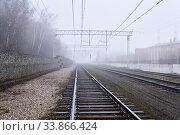 Купить «Railroad rails lurking in fog in perspective», фото № 33866424, снято 27 апреля 2020 г. (c) Евгений Харитонов / Фотобанк Лори