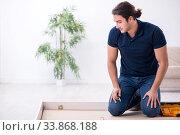 Купить «Young male contractor installing furniture at home», фото № 33868188, снято 11 ноября 2019 г. (c) Elnur / Фотобанк Лори